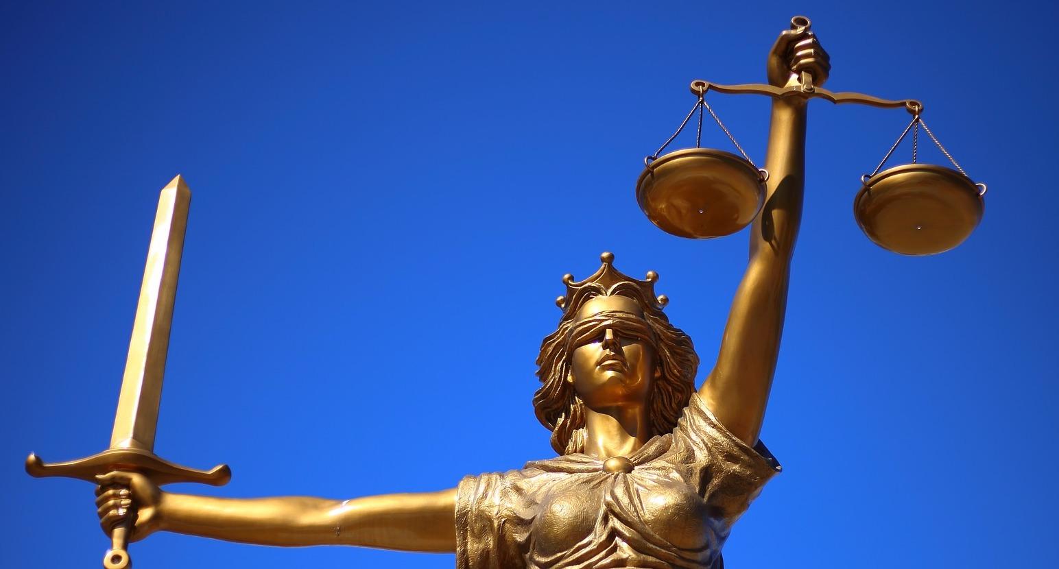 Foto af statue af retfærdighedens gudinde Justicia med sværdet i den ene hånd og vægten med de to skåle i den venstre hånd.
